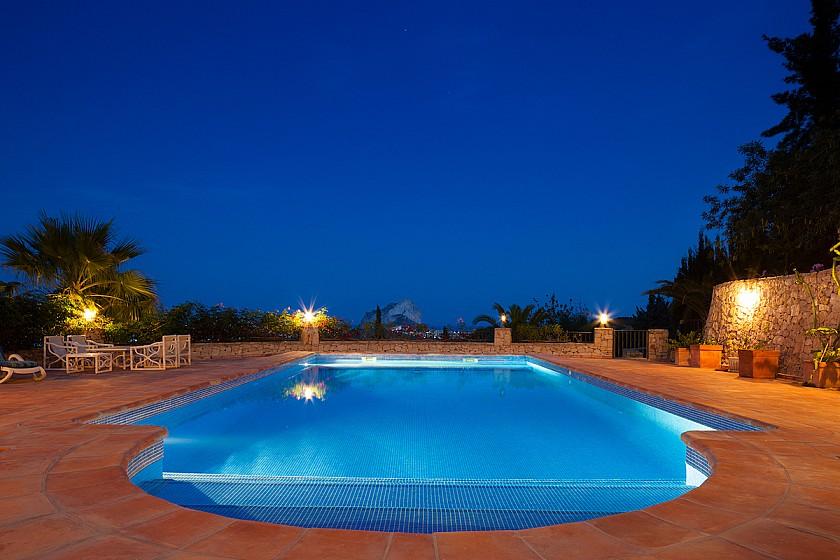 Vista nocturna piscina en mansión de lujo.
