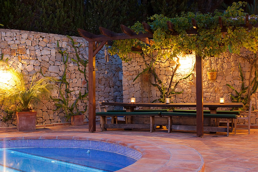Vistas noche zona descanso en piscina.